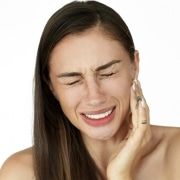 Woman holds fingers on her cheek showing toothache